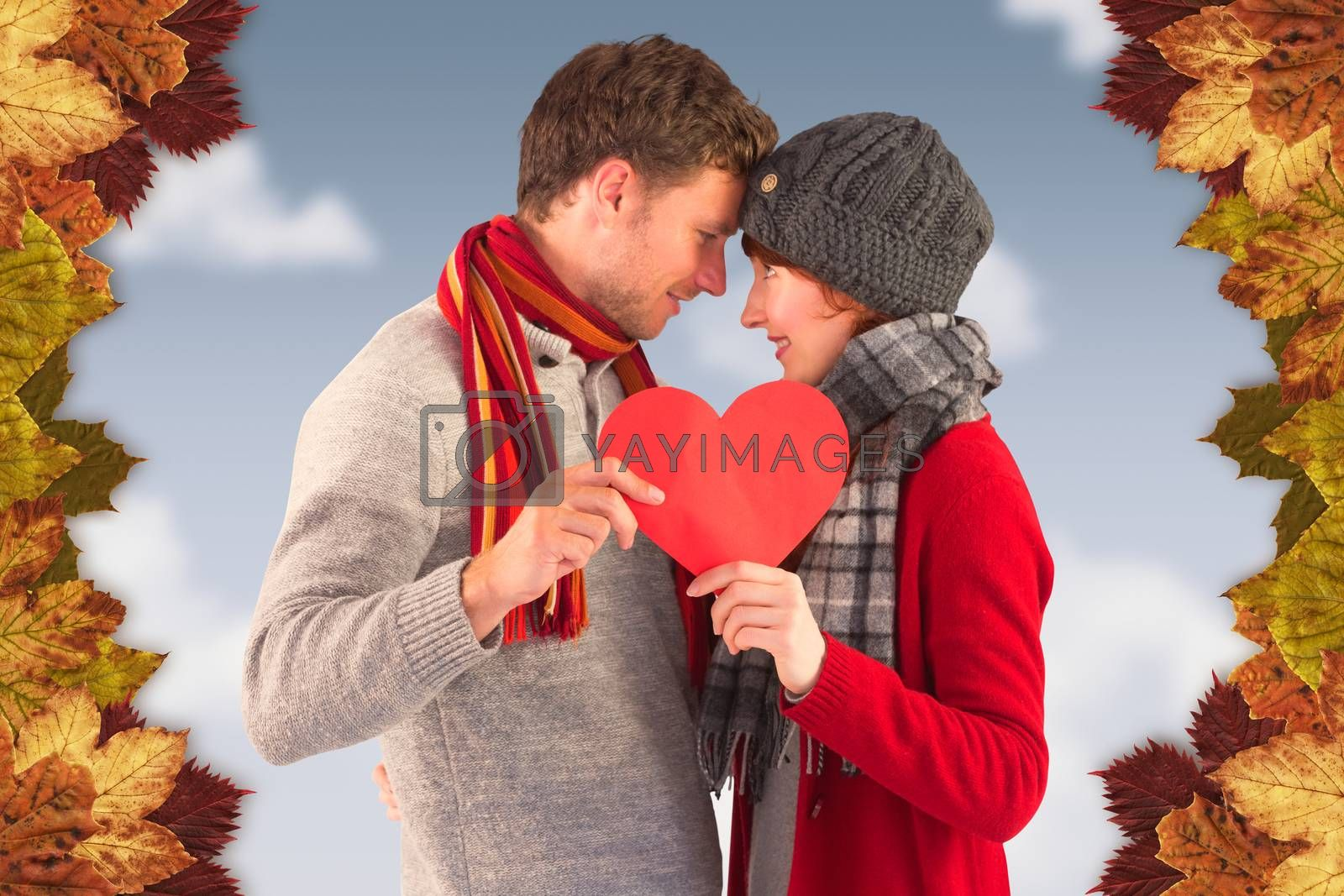Couple holding a red heart against blue sky