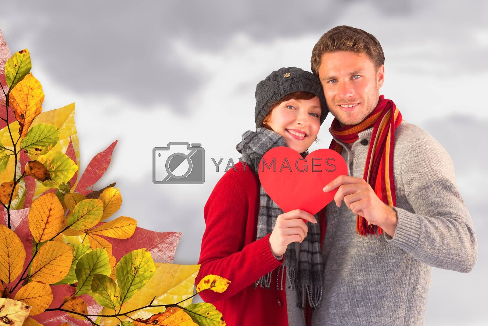Couple holding a red heart against grey cloudy sky