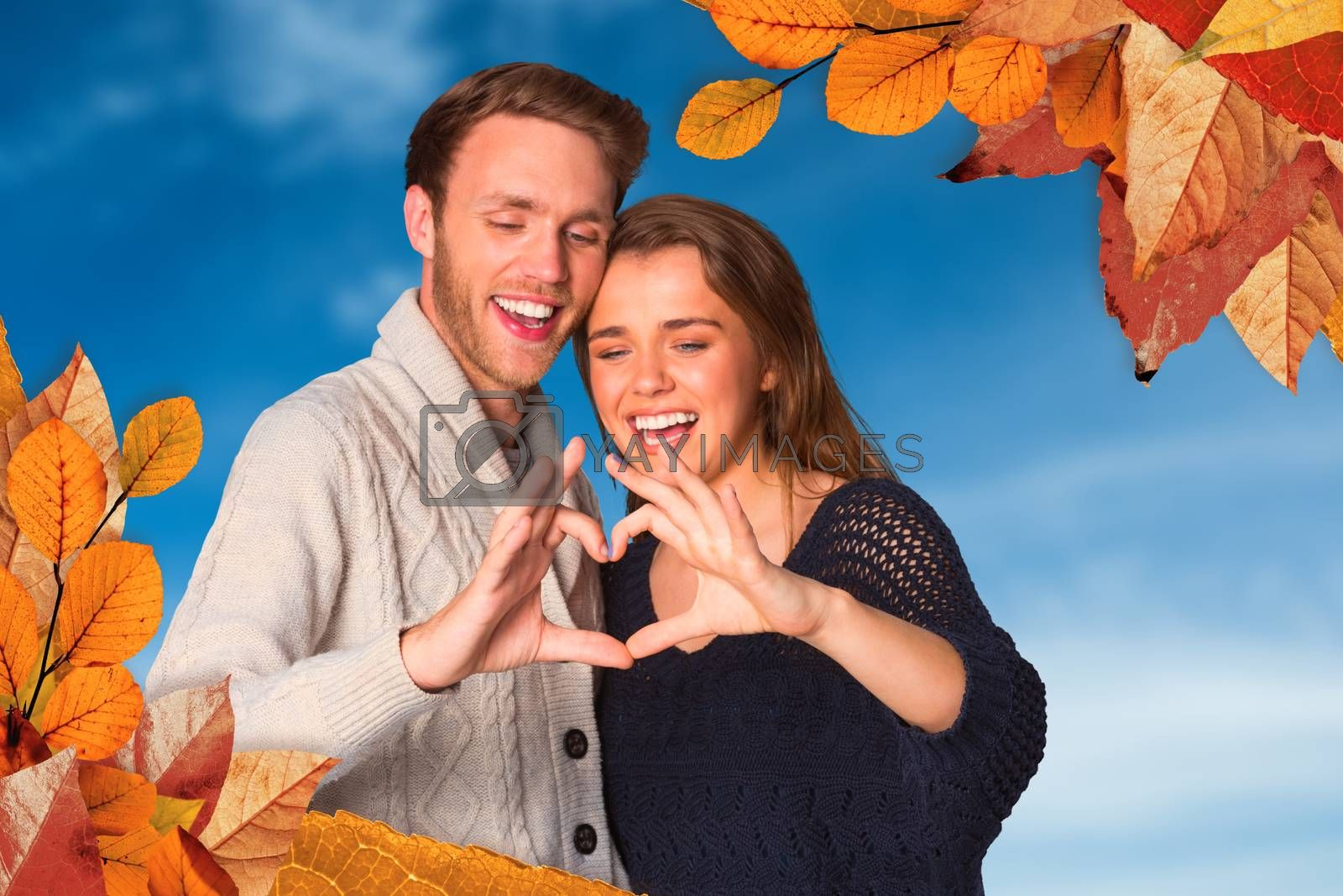 Happy couple forming heart with hands against blue sky