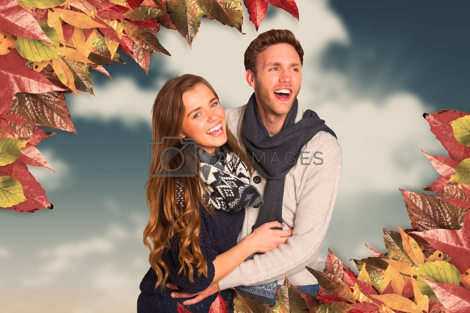 Happy young couple embracing against blue sky