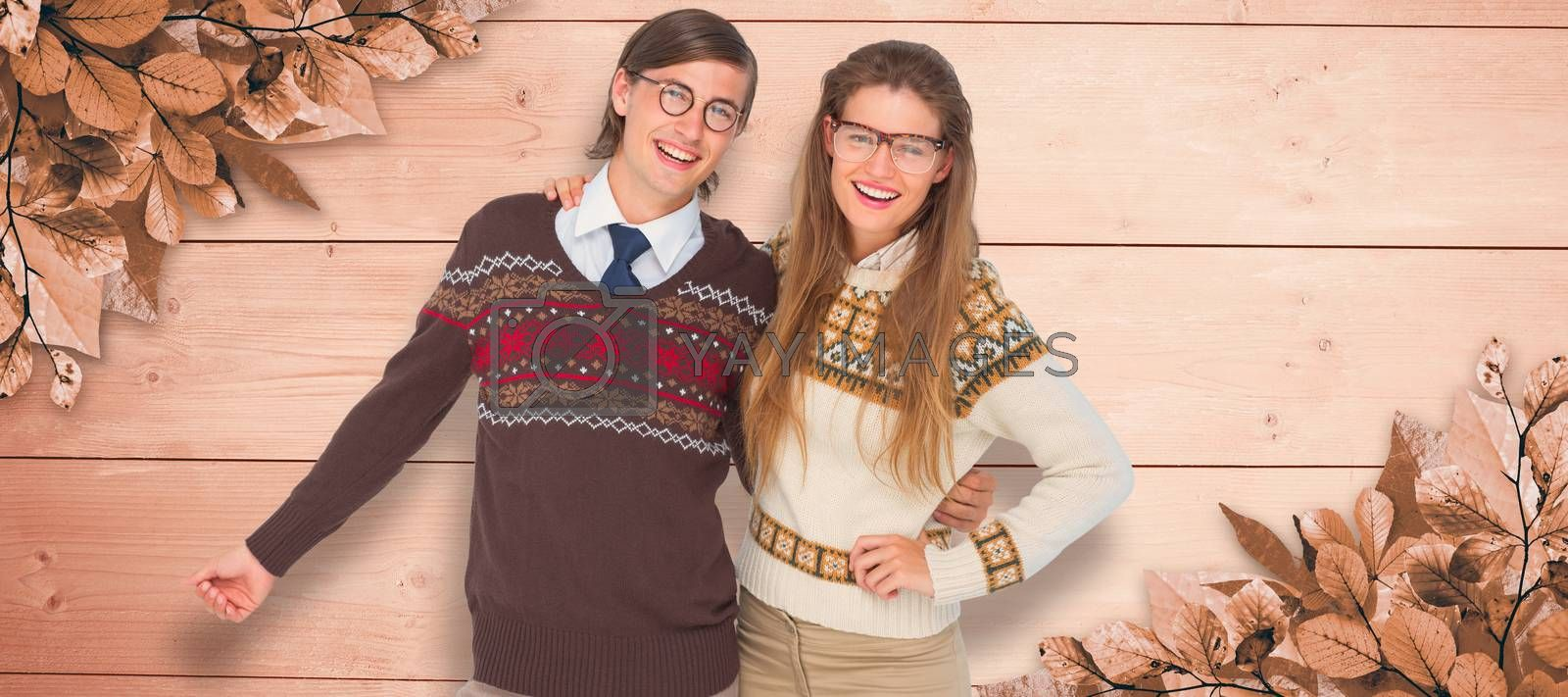 Happy geeky hipster couple embracing against overhead of wooden planks