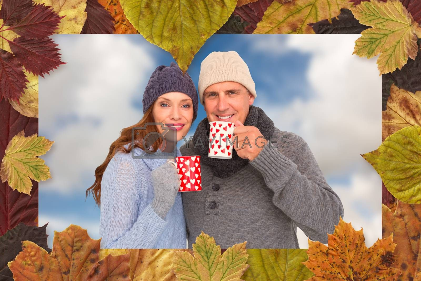 Happy couple in warm clothing holding mugs against blue sky with white clouds