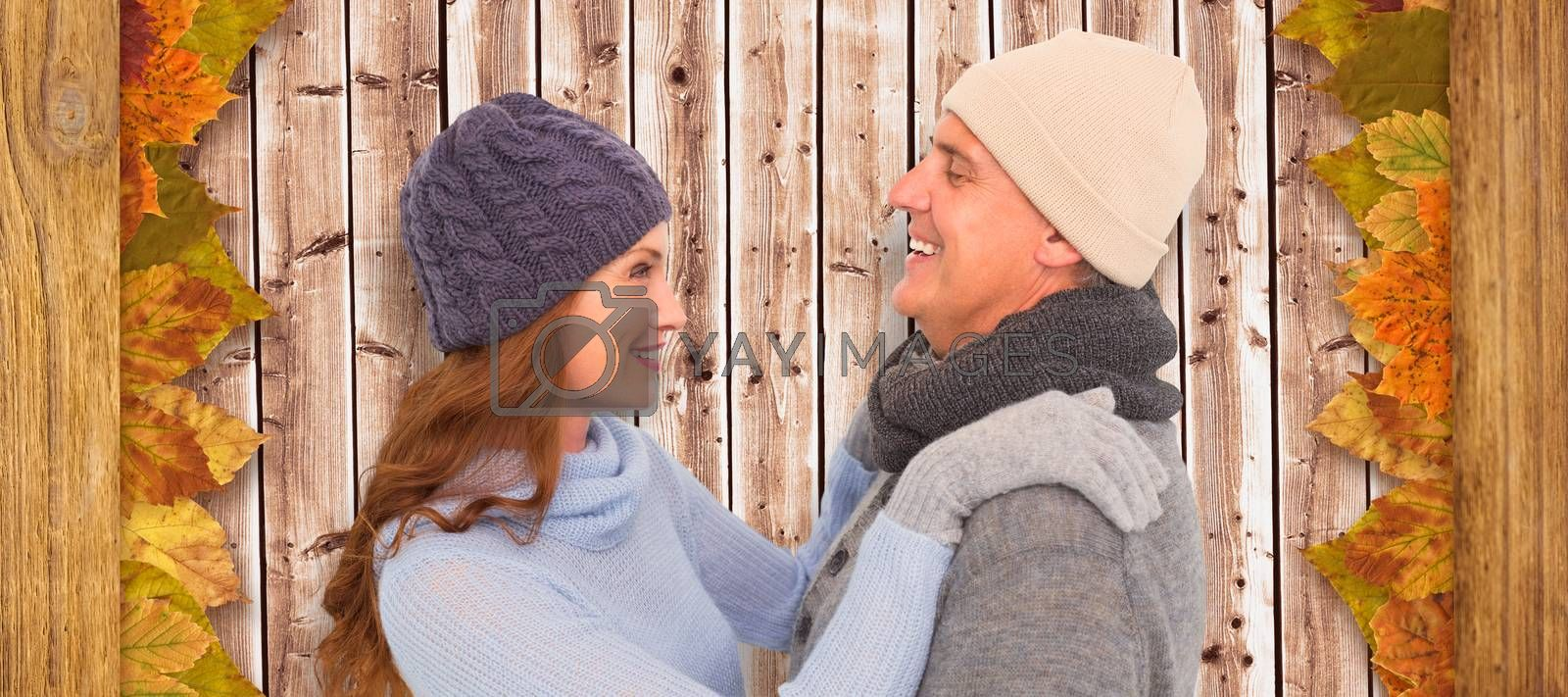 Happy couple in warm clothing against wooden planks background
