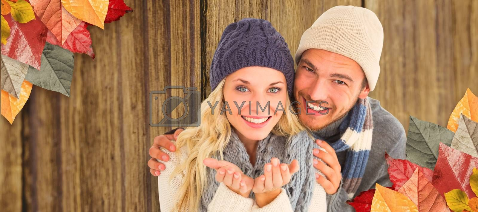 Attractive couple in winter fashion smiling at camera against close-up of wooden plank