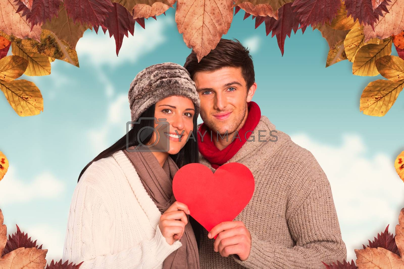 Young couple smiling holding red heart against blue sky