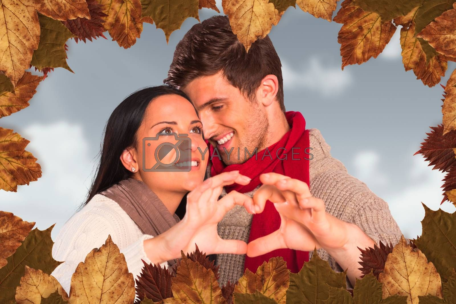 Young couple making heart with hands against blue sky