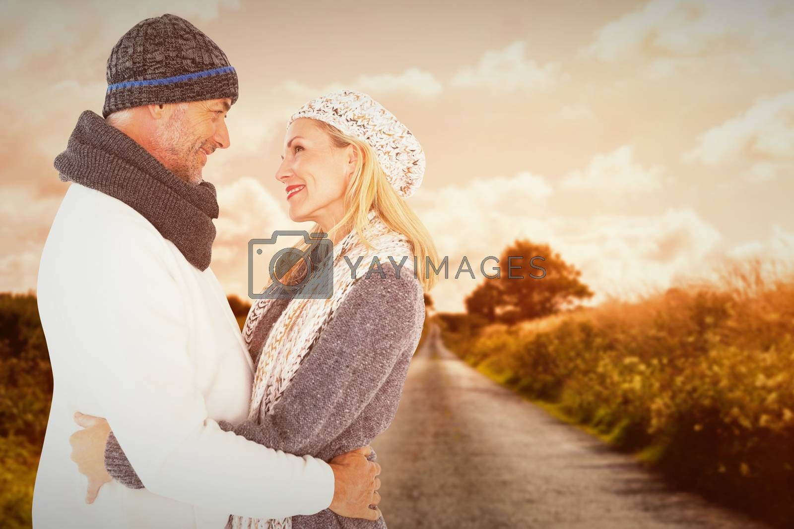Happy husband holding wife while looking at each other against country road