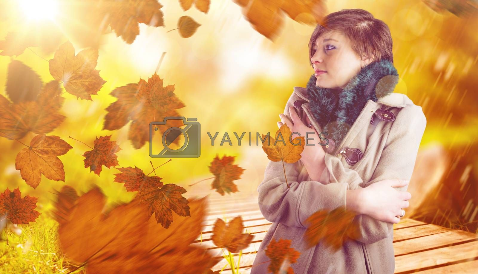 Thoughtful woman in winter coat against wooden trail across countryside