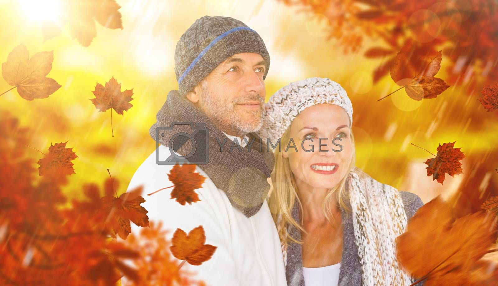 Cheerful couple in warm clothing against wooden trail across countryside