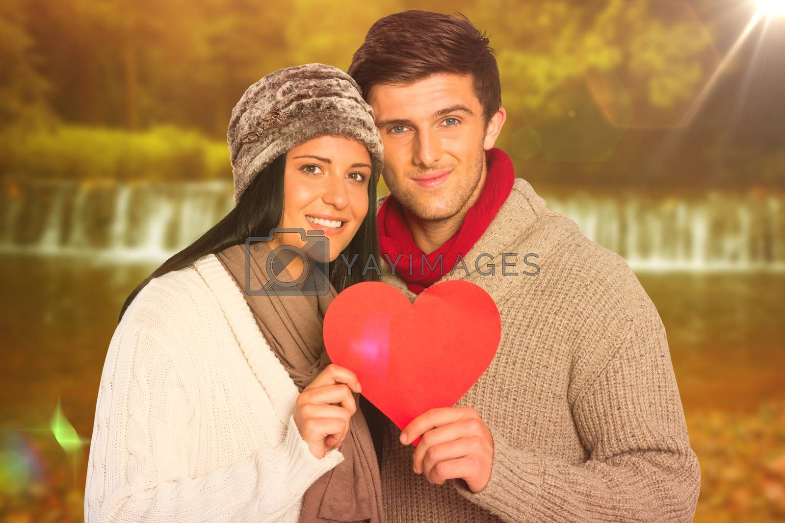 Composite image of young couple smiling holding red heart by Wavebreakmedia