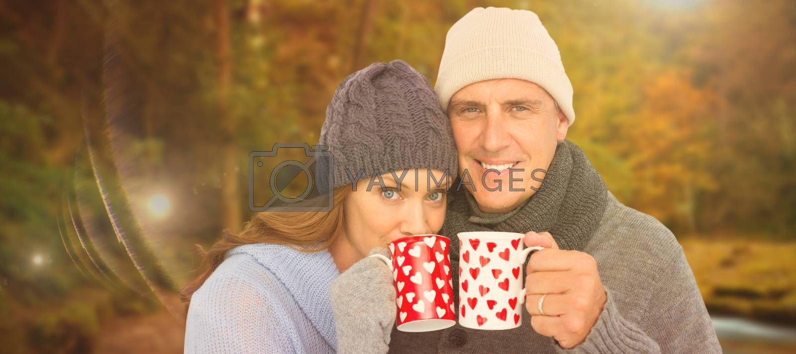 Happy couple in warm clothing holding mugs against autumn scene