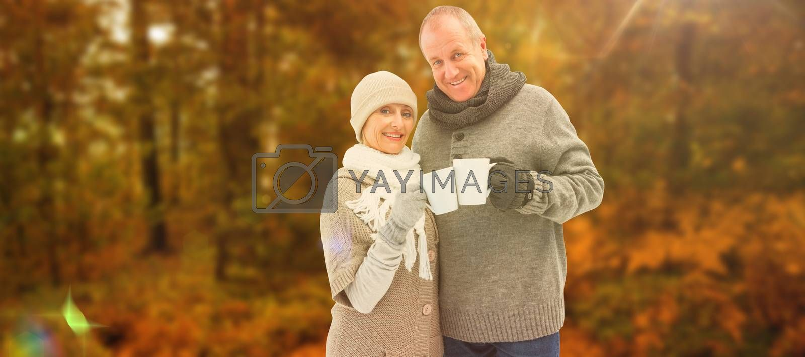 Happy mature couple in winter clothes holding mugs against autumn scene
