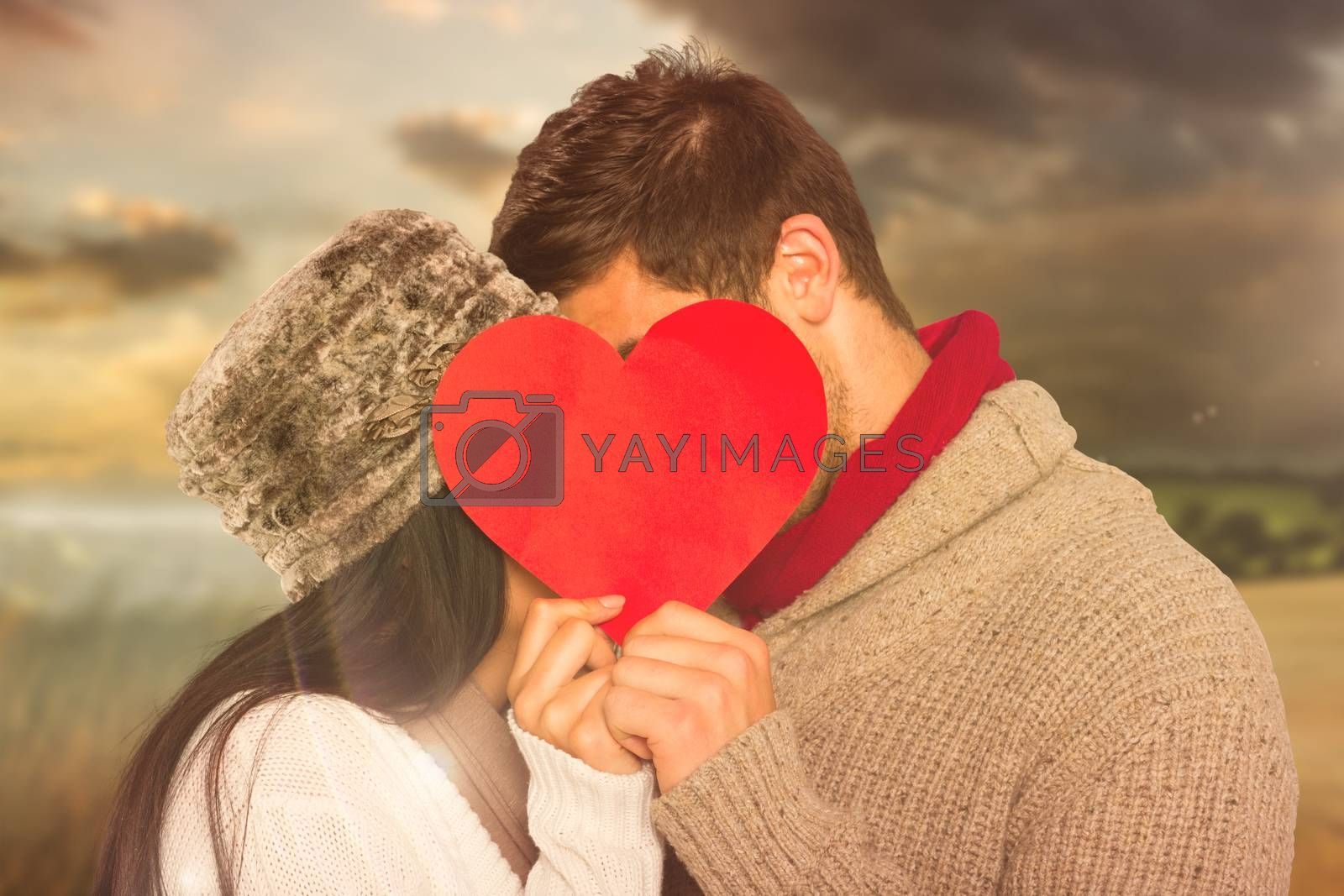 Young couple kissing behind red heart against country scene