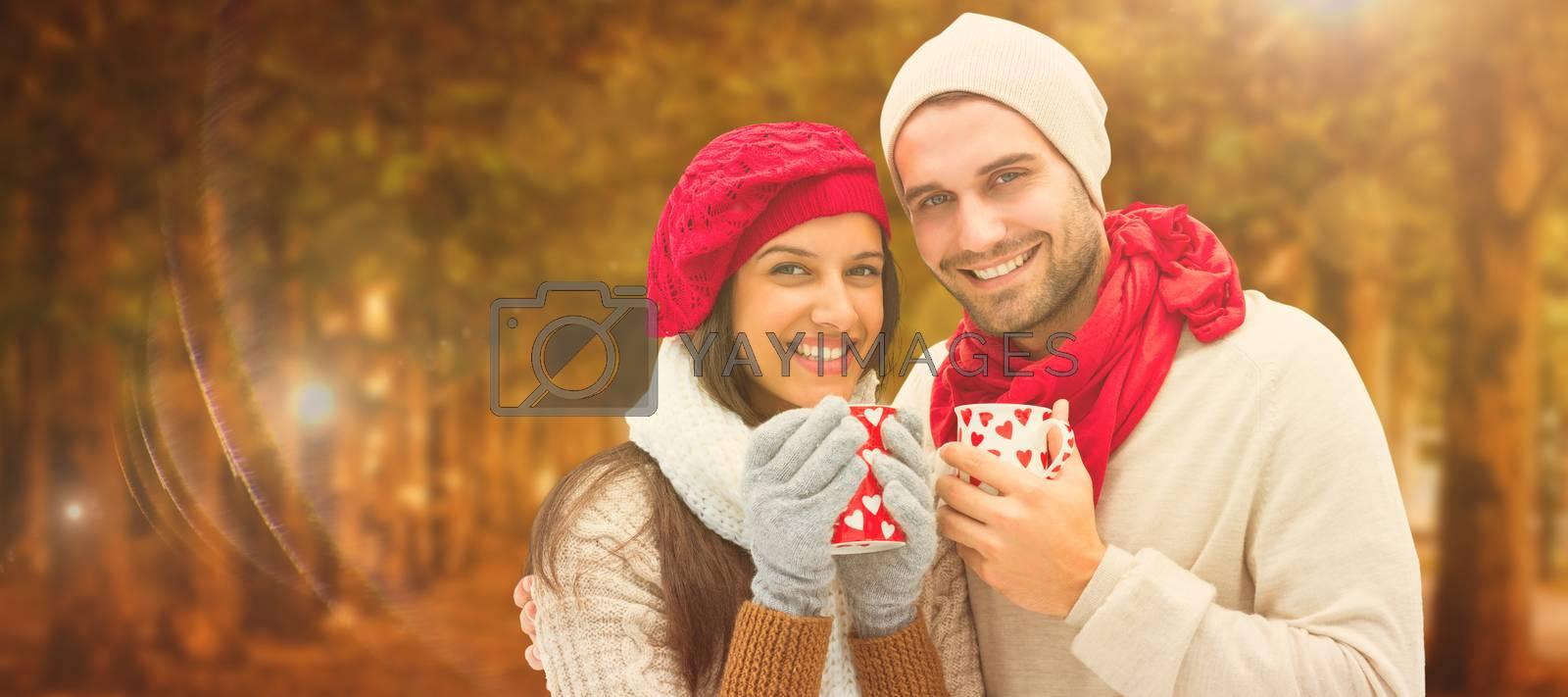Winter couple holding mugs against autumn scene