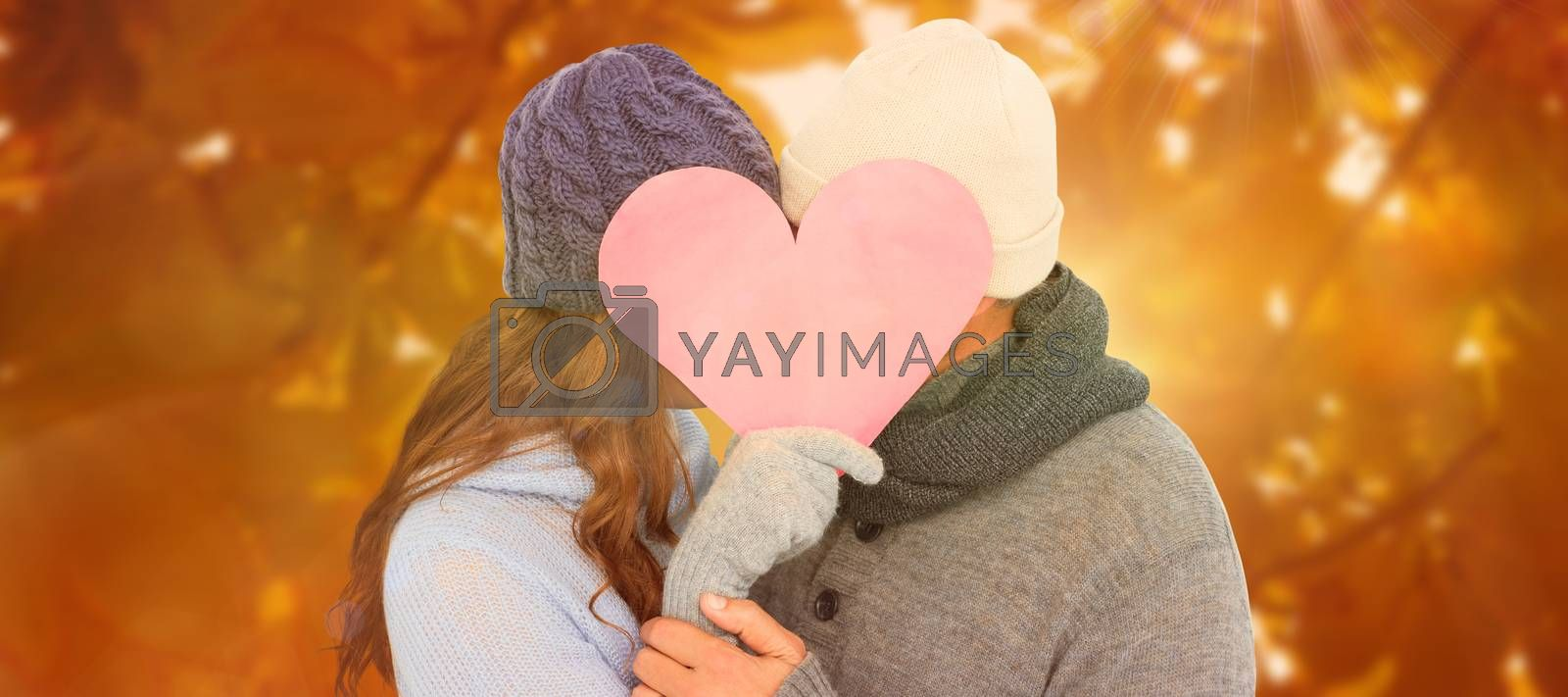 Couple in warm clothing holding heart against autumn scene