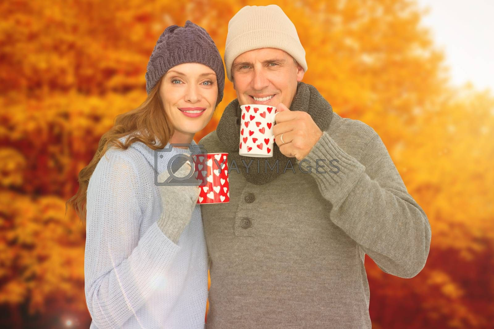 Composite image of happy couple in warm clothing holding mugs by Wavebreakmedia