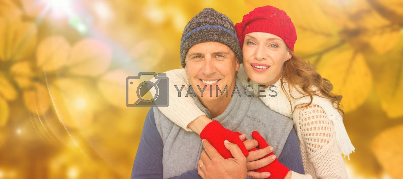 Happy couple in warm clothing against autumn scene