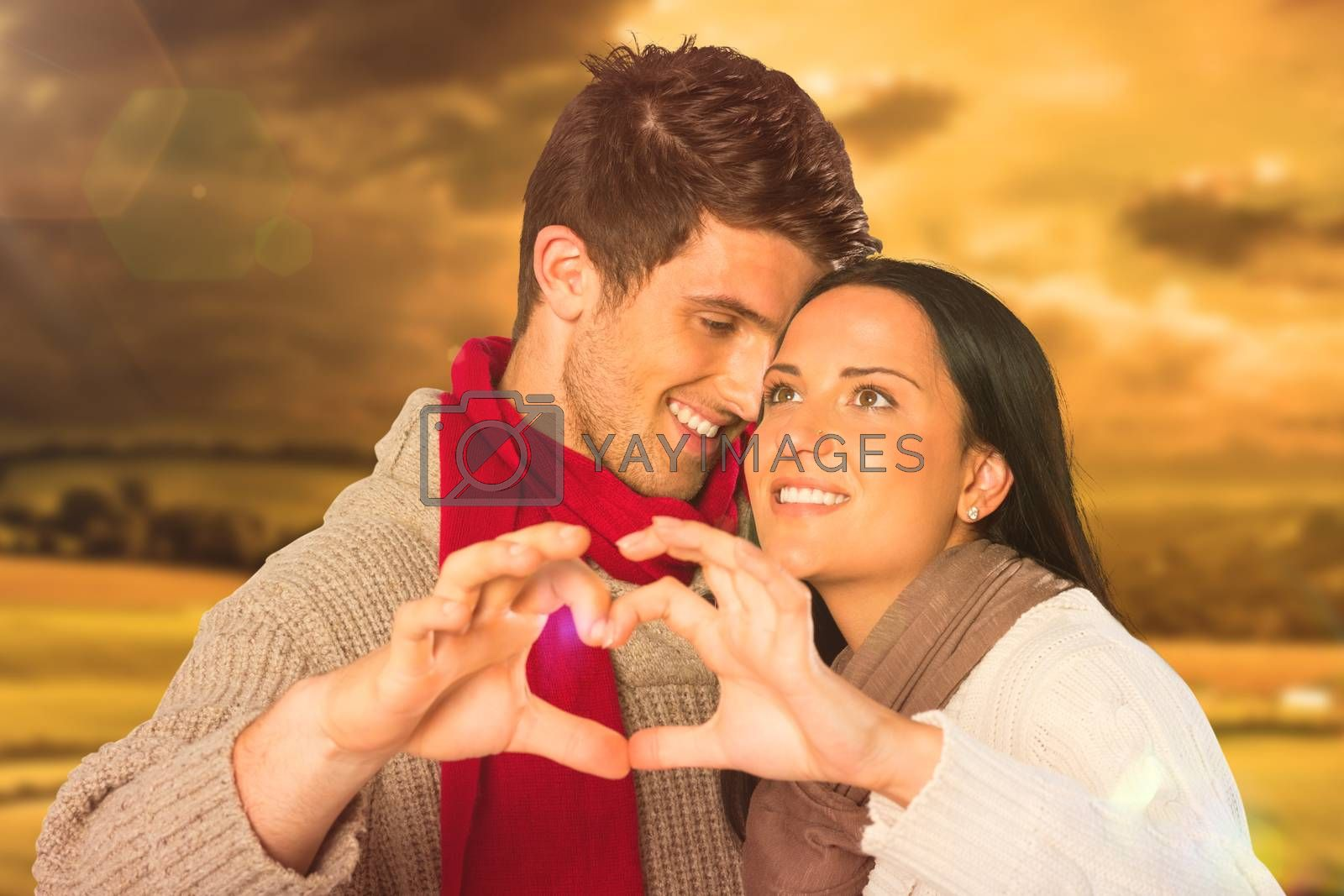 Young couple making heart with hands against country scene