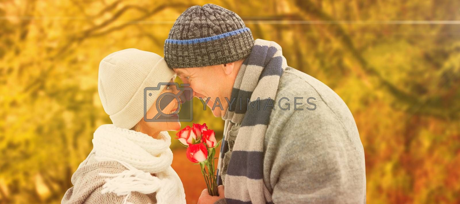 Composite image of happy mature couple in winter clothes with roses by Wavebreakmedia