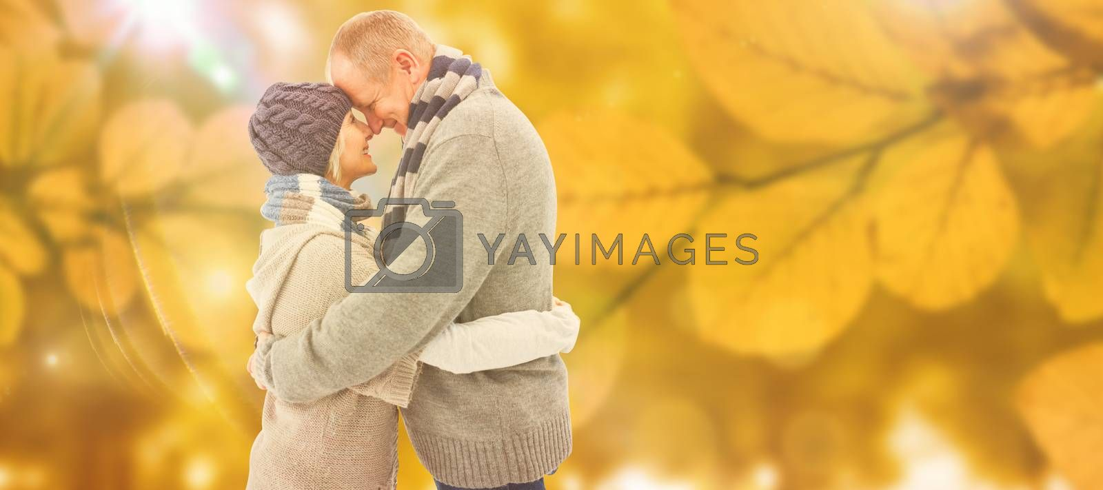 Happy mature couple in winter clothes hugging against autumn scene