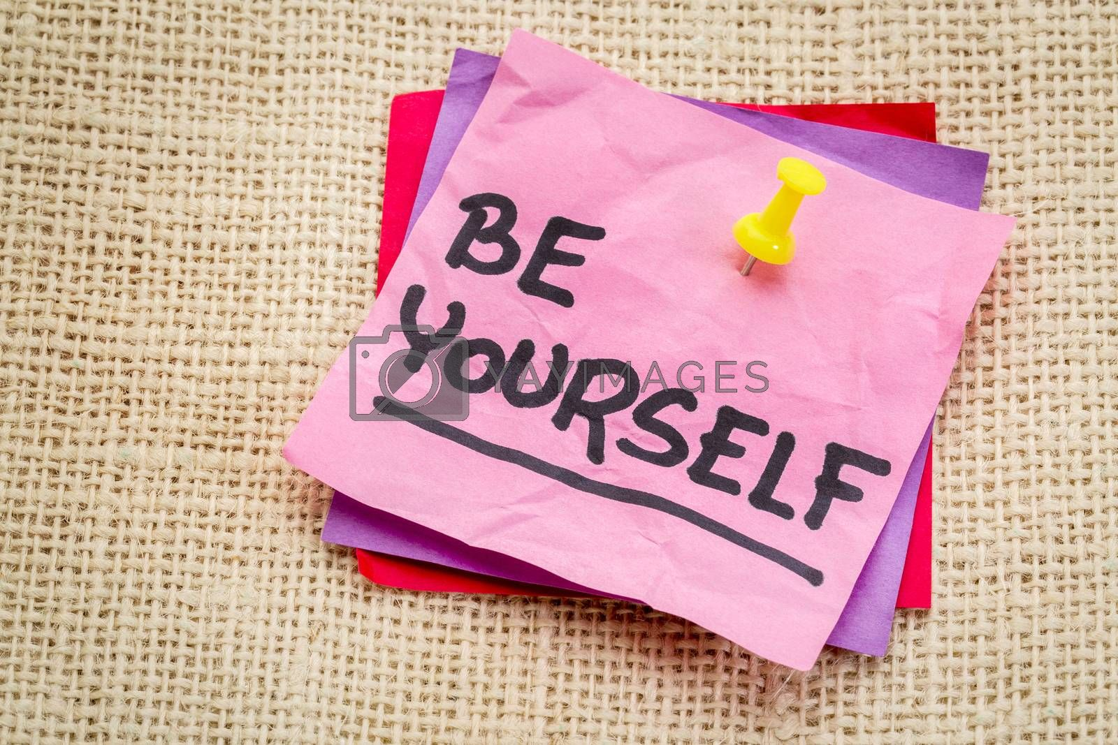 Be yourself reminder or advice on a sticky note against burlap canvas