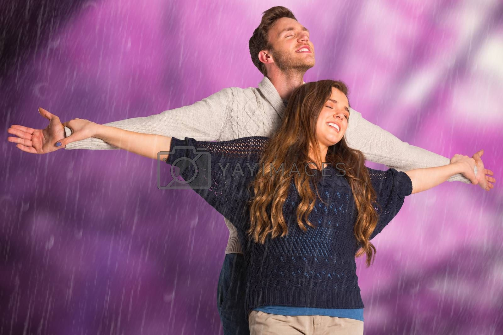 Romantic young couple with arms out against colourful forest