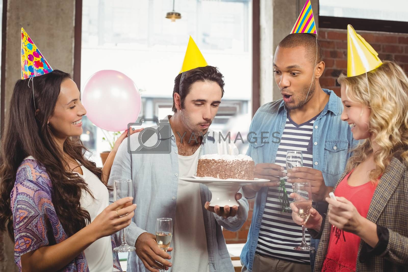 Man blowing candle on cake while colleagues smiling in office