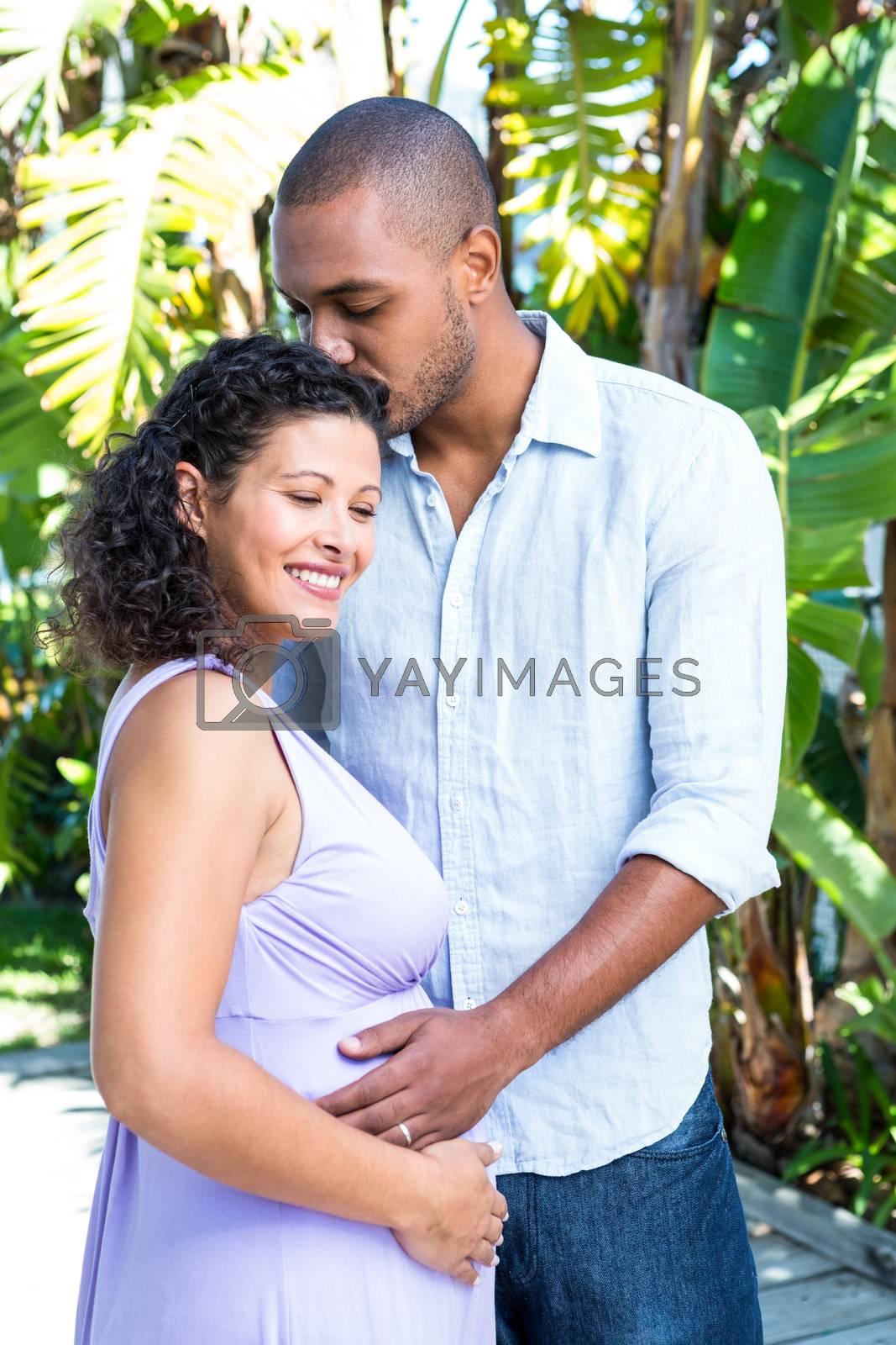 Husband kissing pregnant wife head in yard
