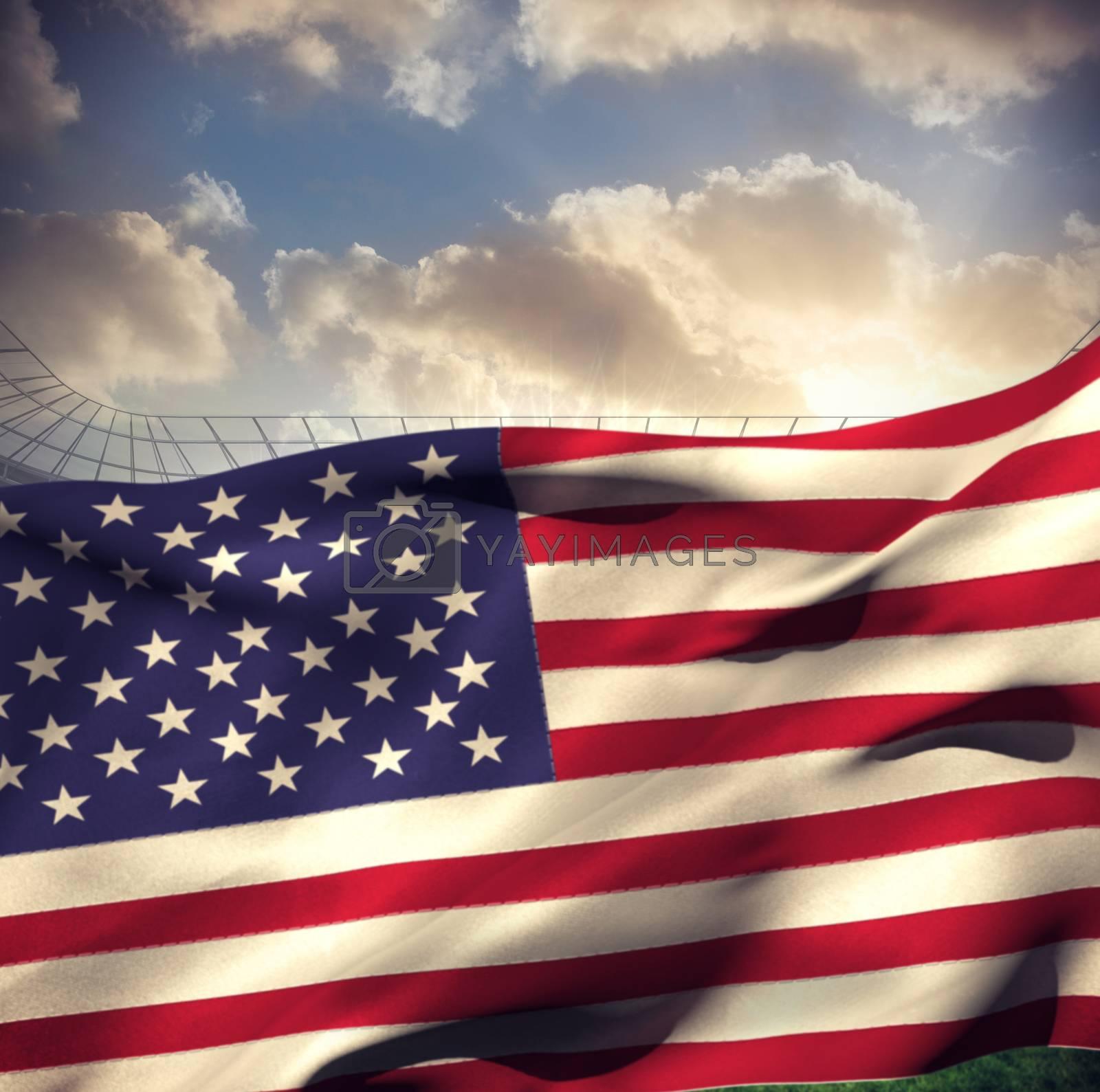 Waving American flag against large football stadium under cloudy blue sky