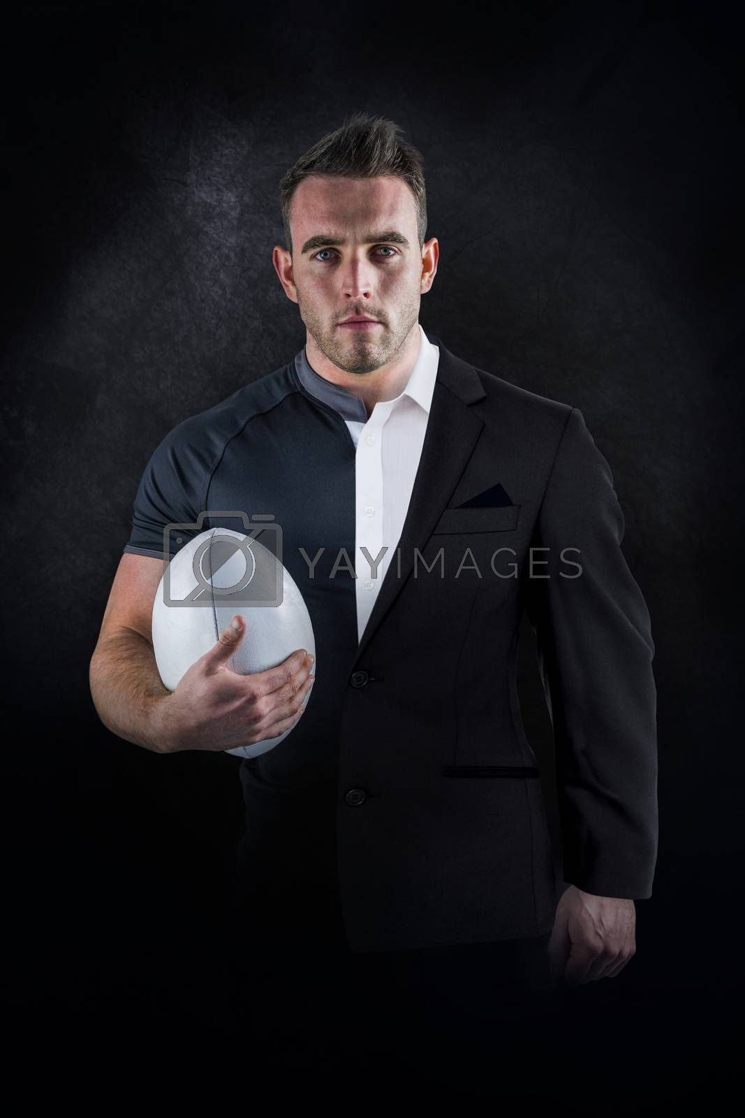 Tough rugby player holding ball against half a suit