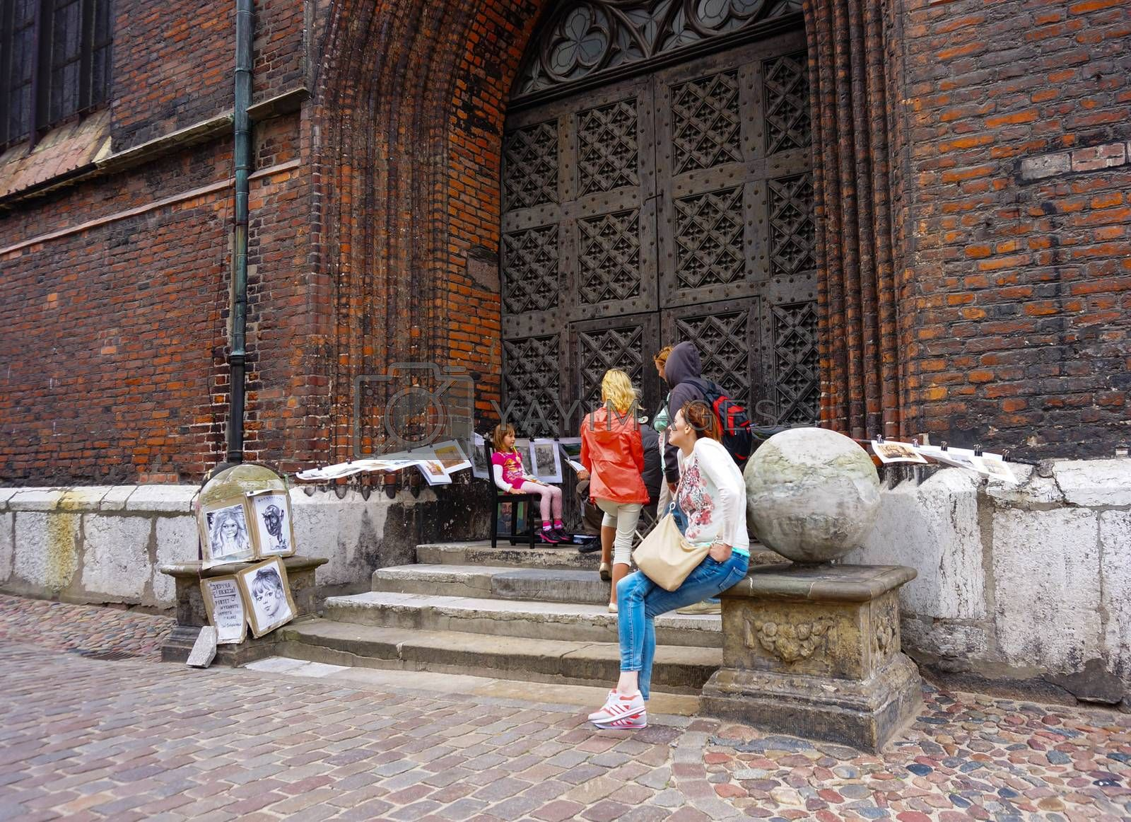 GDANSK, POLAND - JULY 29, 2015: People sitting in front of a cathedral entrance
