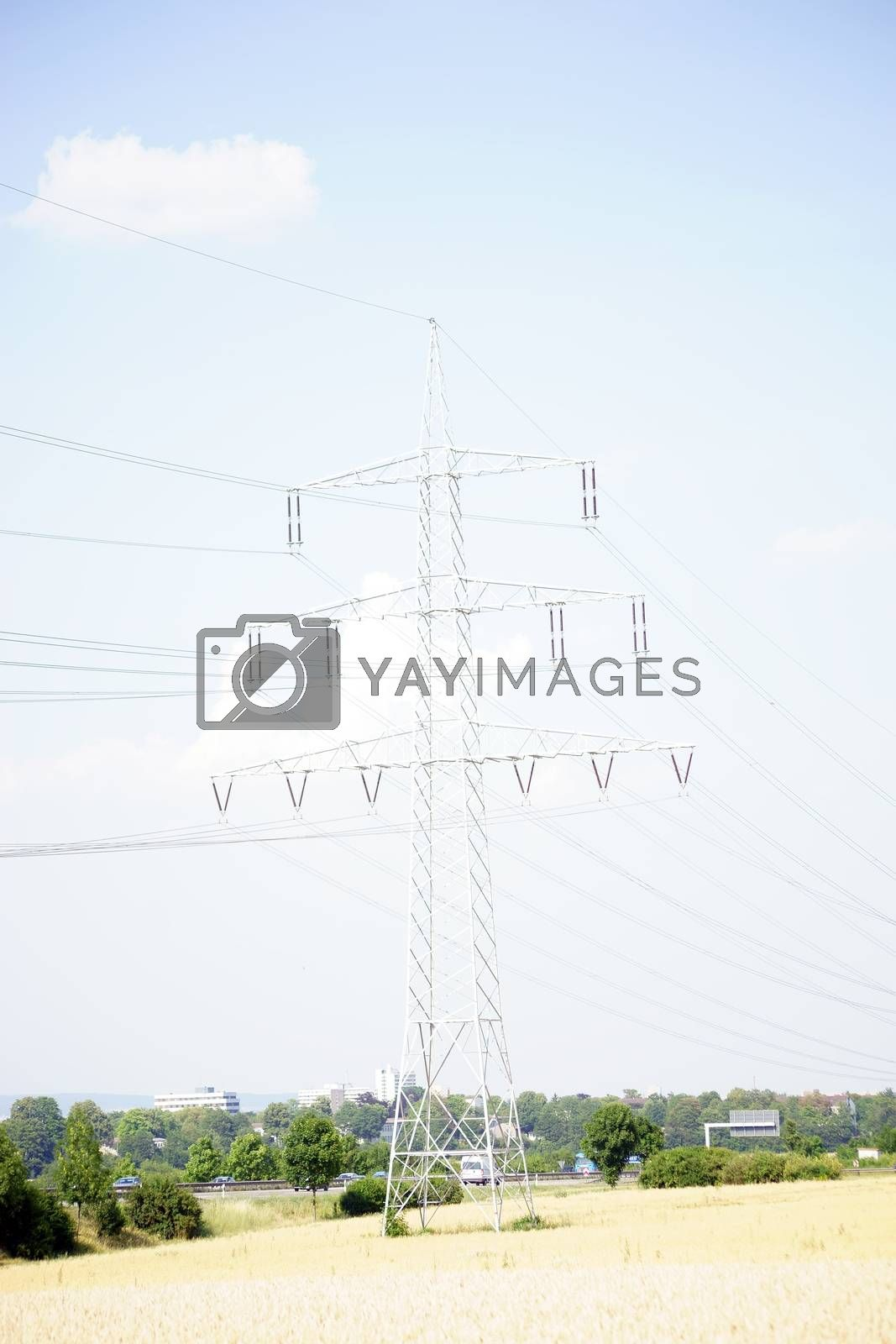 A pole with high-voltage lines on a field in the backlight.