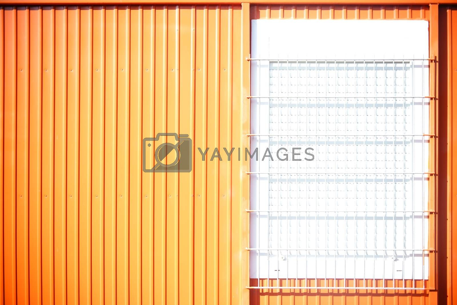 The highly luminous by strong sunlight corrugated metal wall of a Portakabin with a barred window.