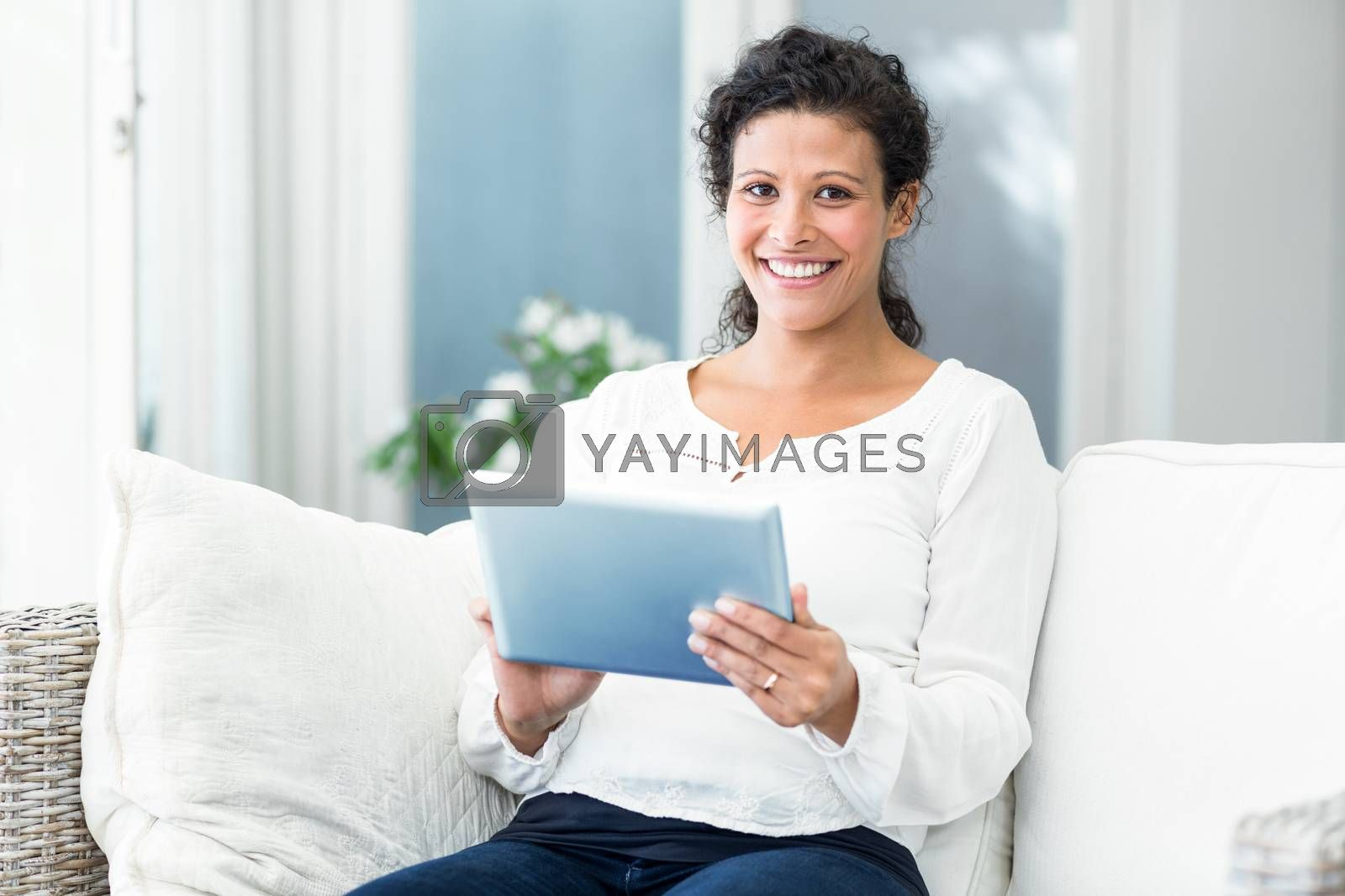 Portrait of happy pregnant woman using tablet while sitting on sofa at home