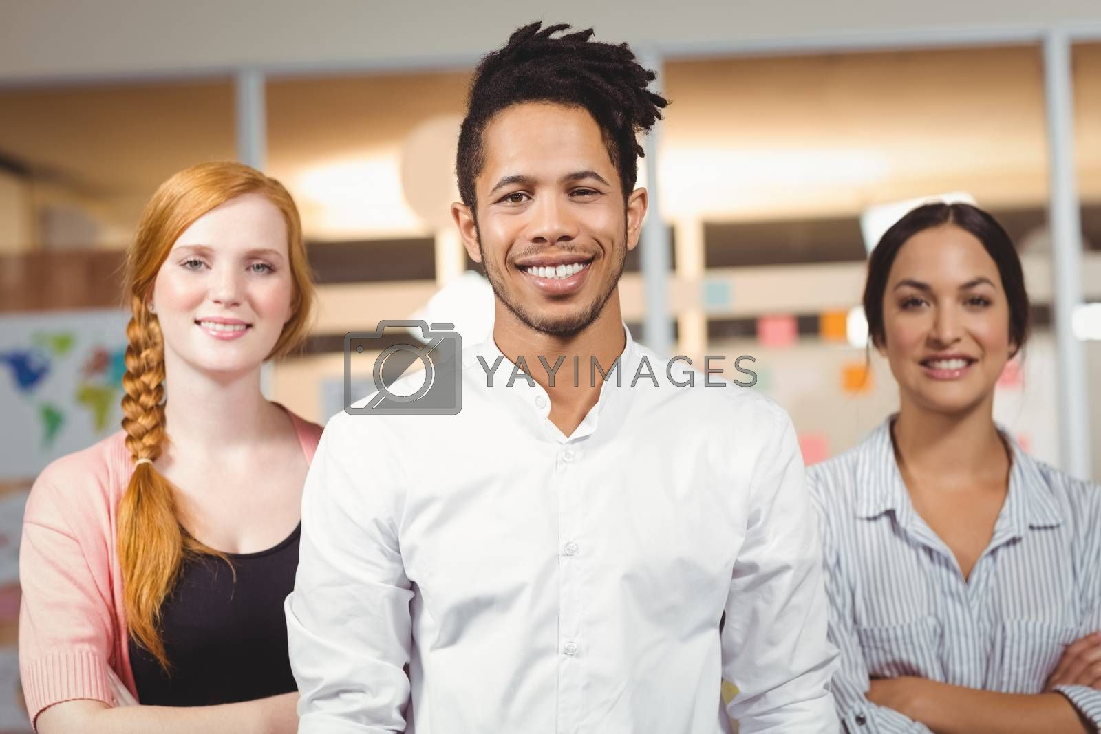 Portrait of confident smiling businessman with female colleagues standing in office
