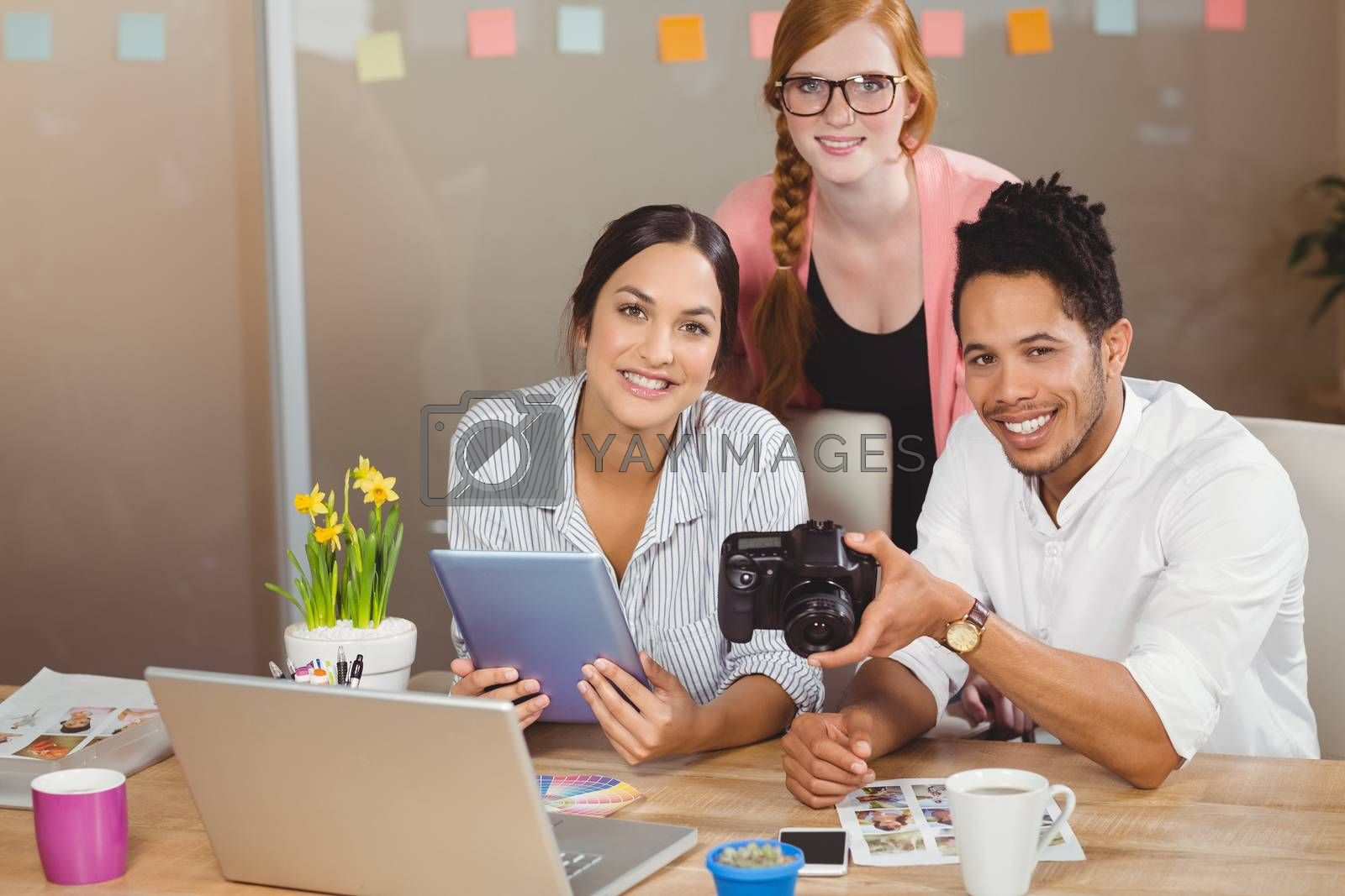 Portrait of happy business people with camera working in creative office