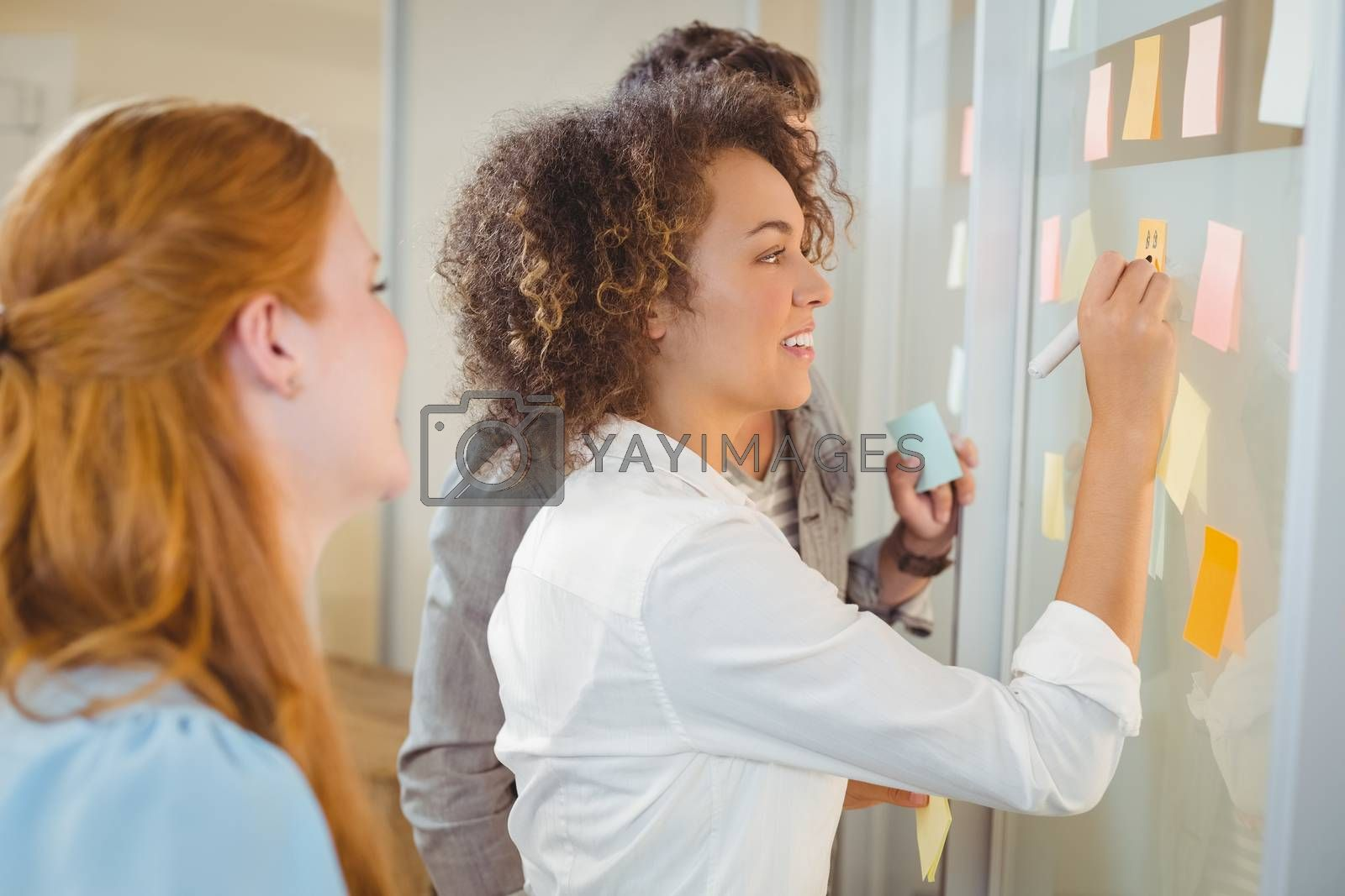 Smiling businesswoman writing on glass as colleagues looking at it during meeting in office