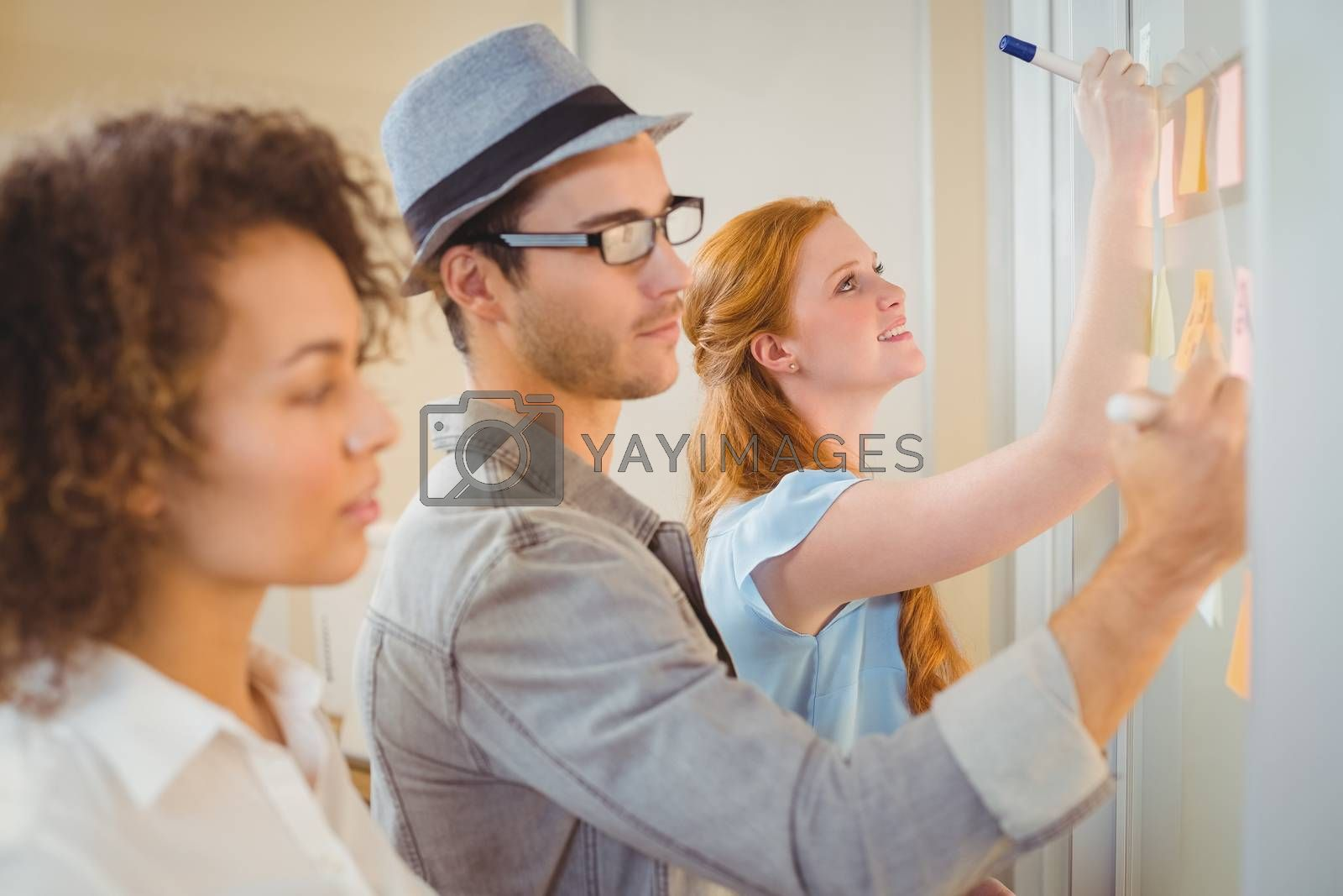 Smiling businesswoman writing on adhesive notes on glass wall during meeting in office