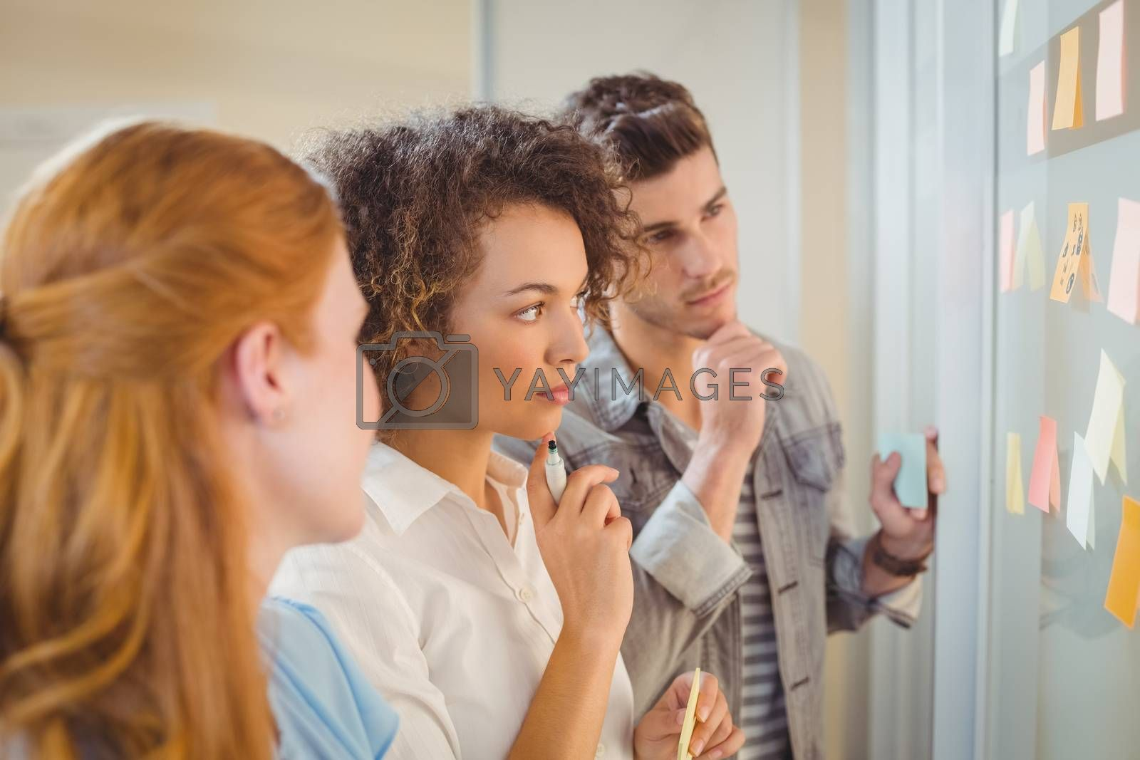 Thoughtful business poeple looking at adhesive notes on glass wall during meeting in office