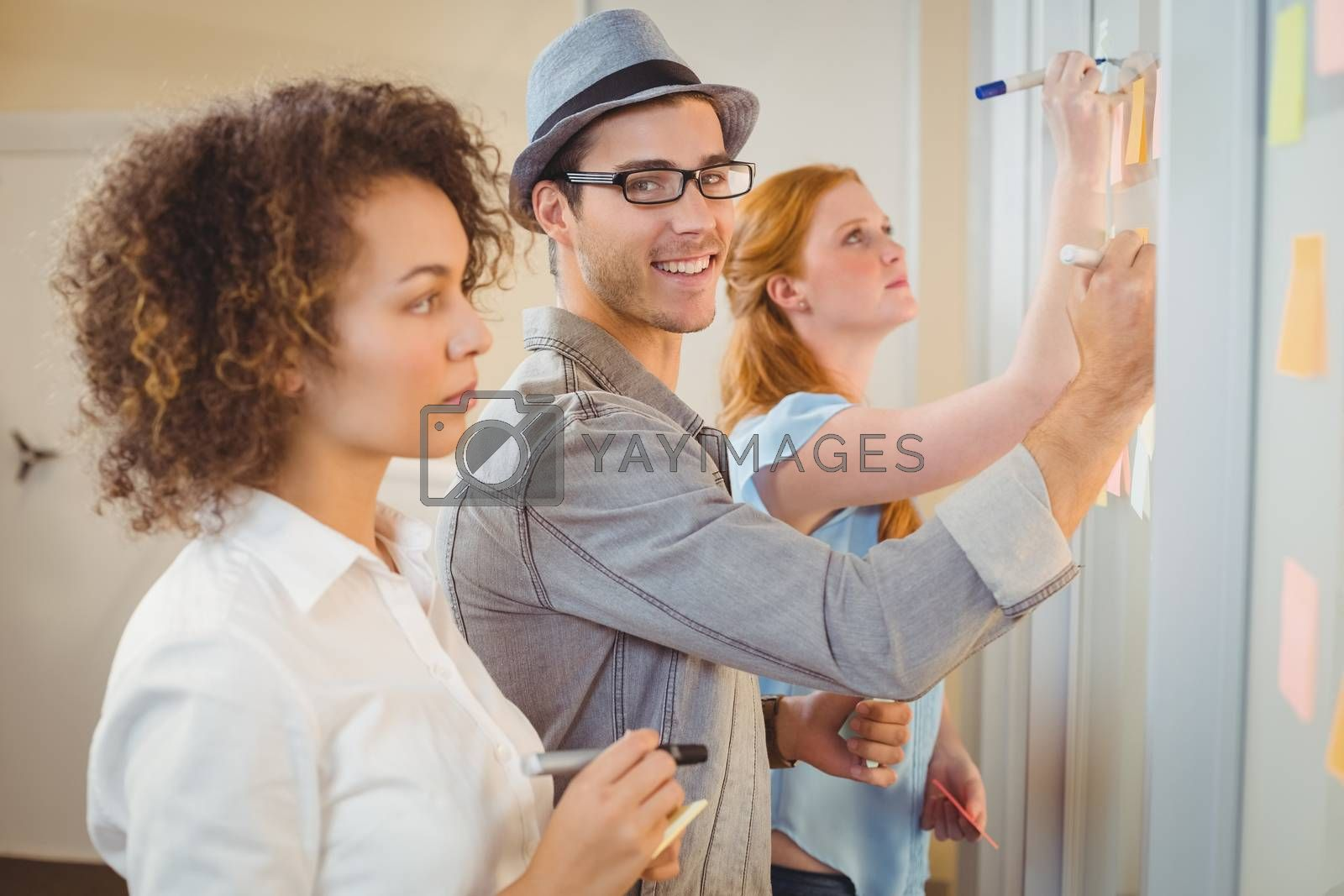 Portrait of smiling businessman writing on adhesive notes on glass wall during meeting with colleagues in office