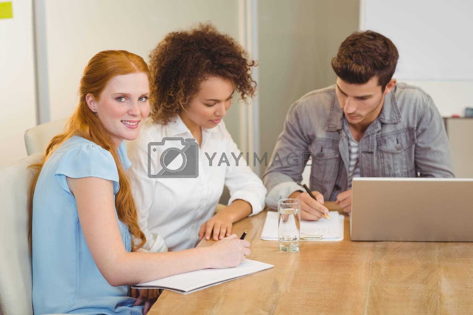 Portrait of smiling businesswoman with colleagues in meeting at office