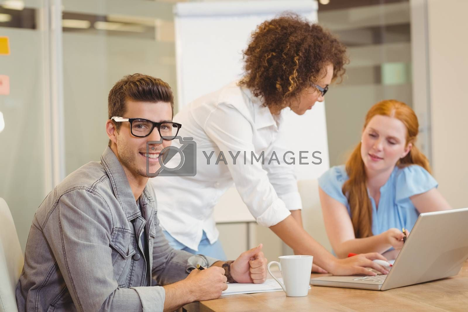 Portrait of handsome businessman wearing eyeglasses in meeting with female colleagues in office