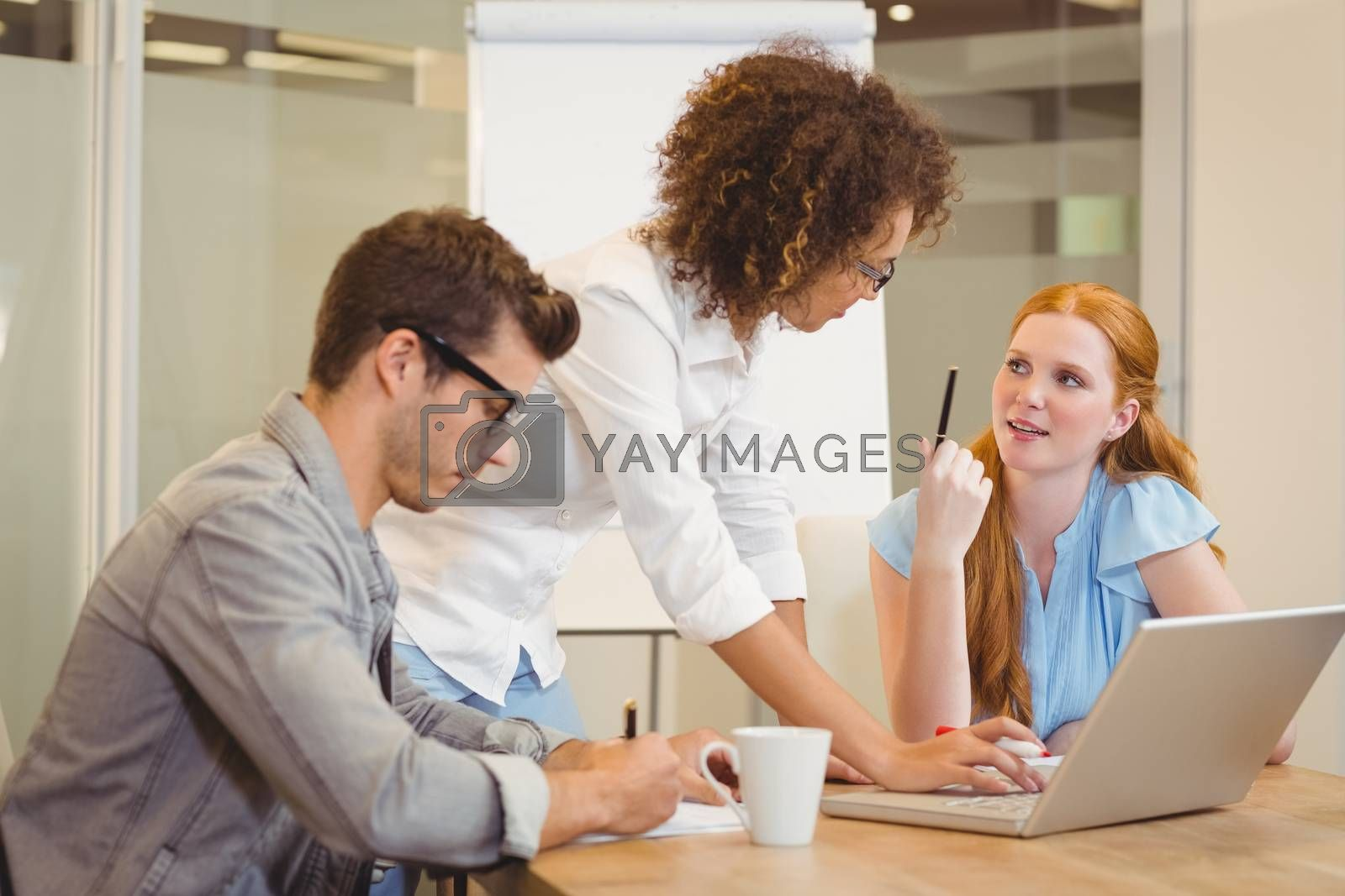 Business people discussing using laptop in meeting at office