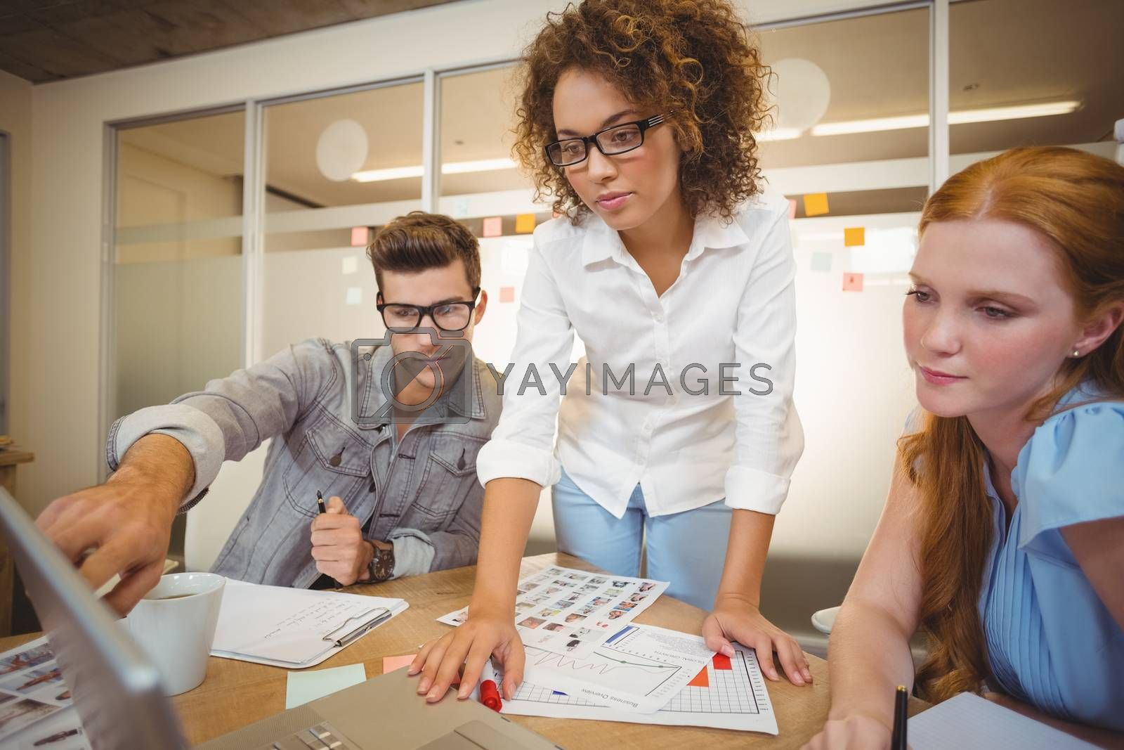 Businessman pointing on laptop as female colleagues looking at it during meeting in office