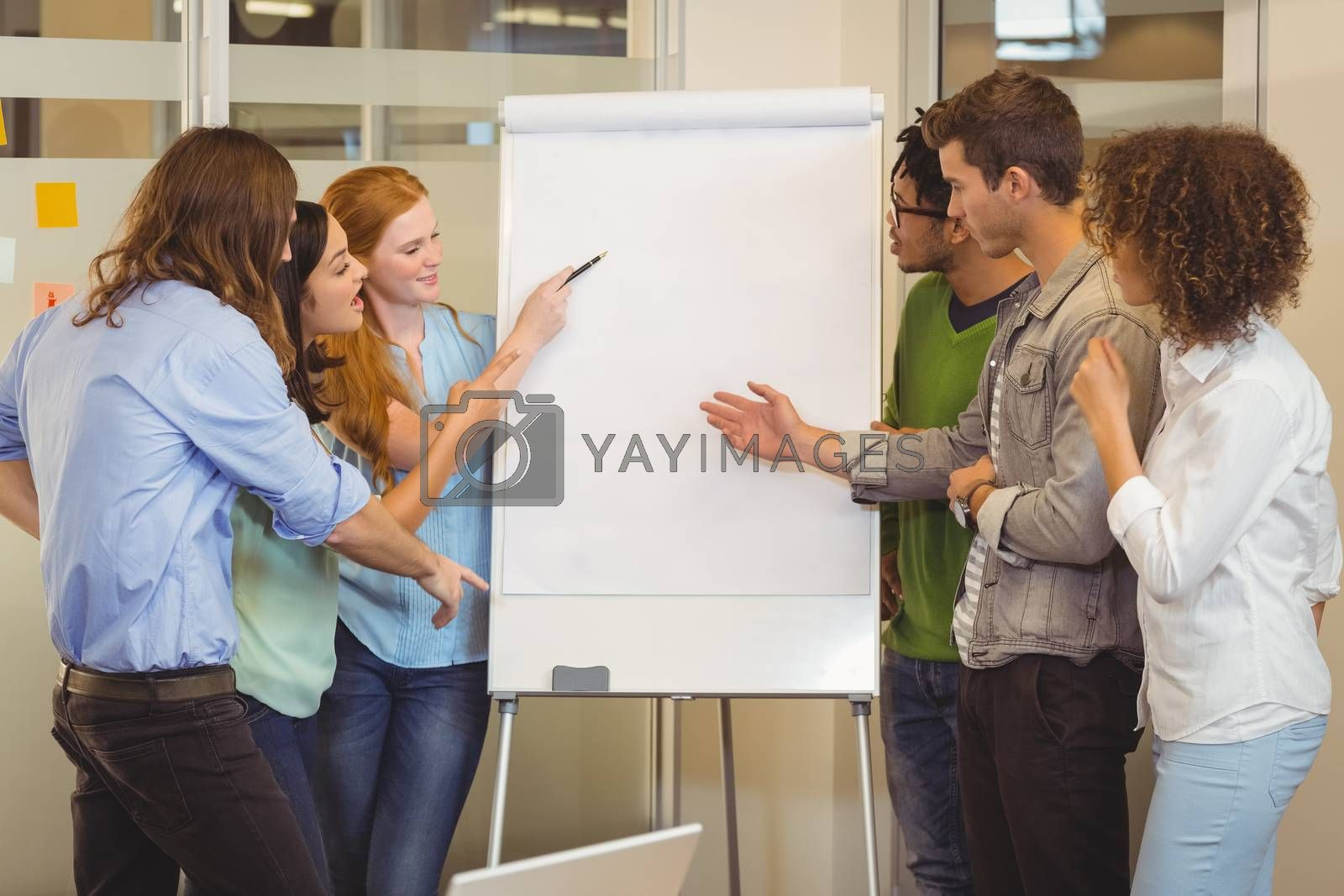 Business people looking at whiteboard during meeting in office