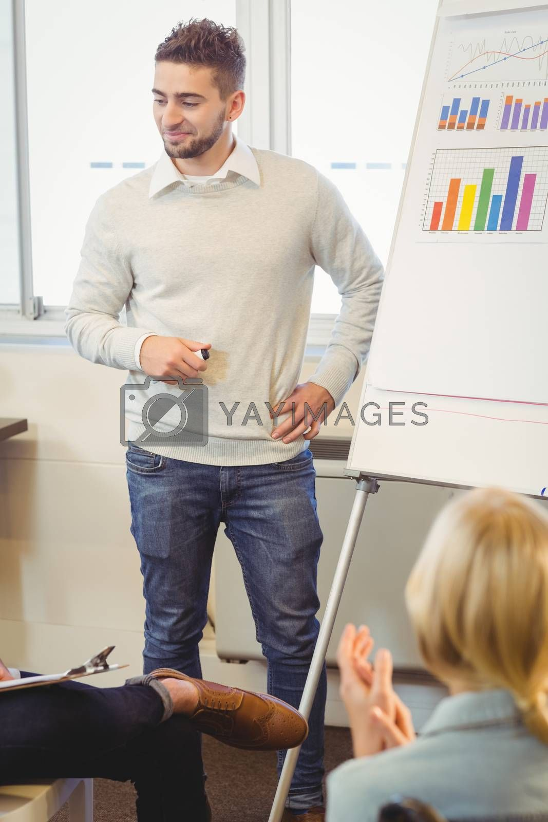 Handsome businessman giving presentation in meeting room at creative office