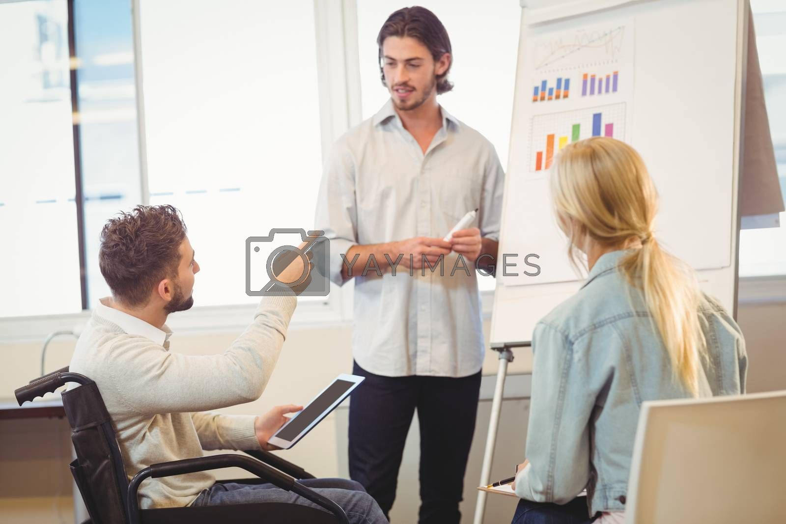 Disabled businessman pointing towards whiteboard while colleagues looking at it during meeting in creative office