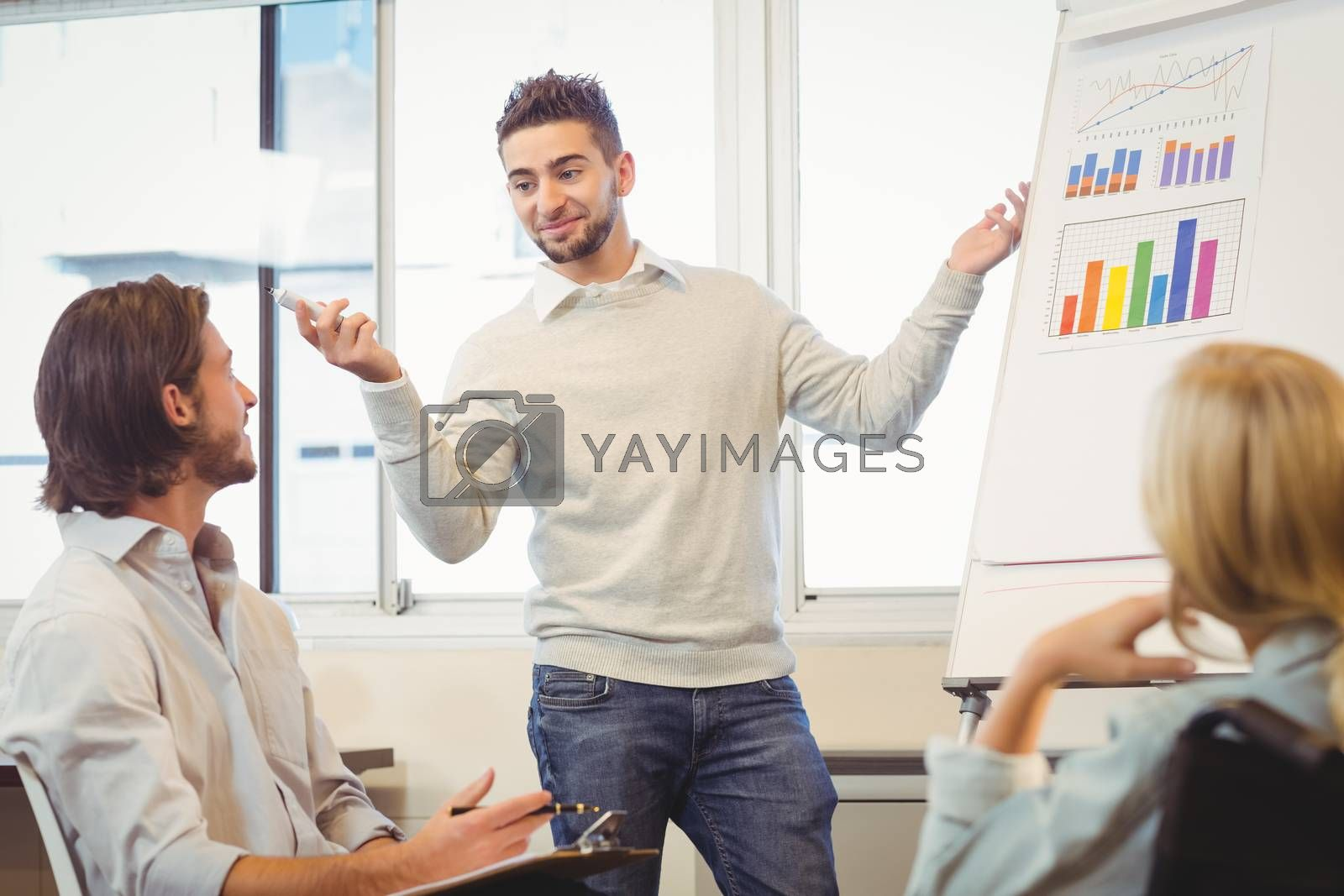 Confident businessman giving presentation in meeting room at creative office