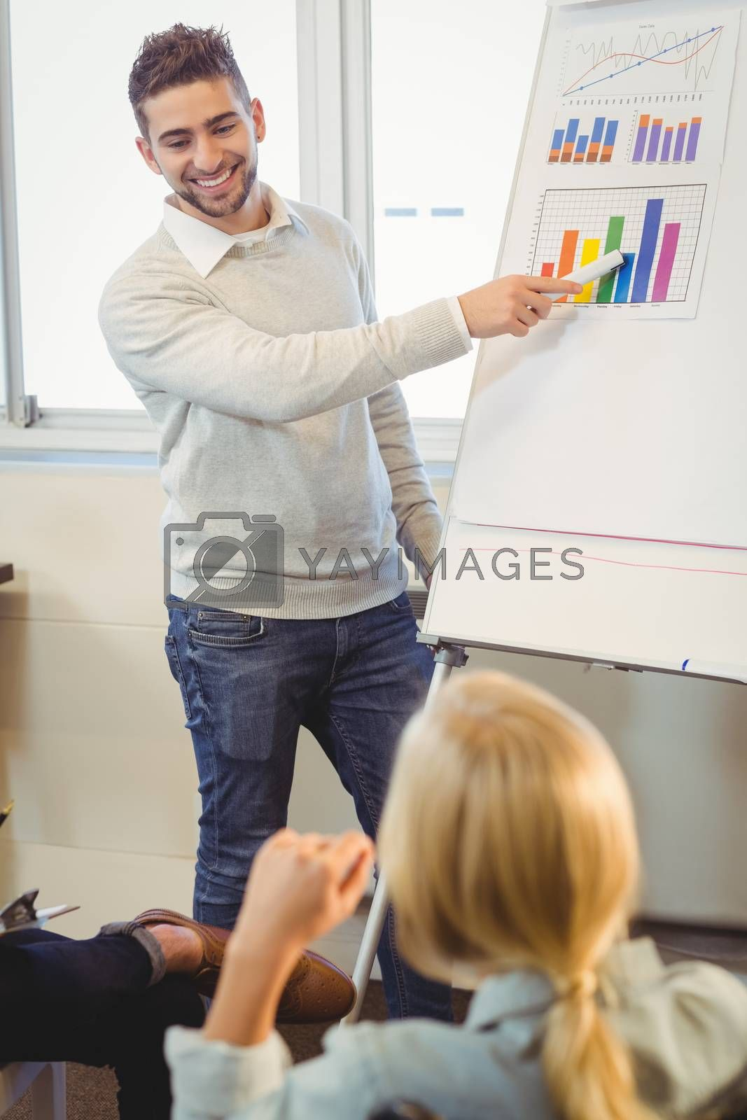 Smiling businessman giving presentation in meeting room at creative office