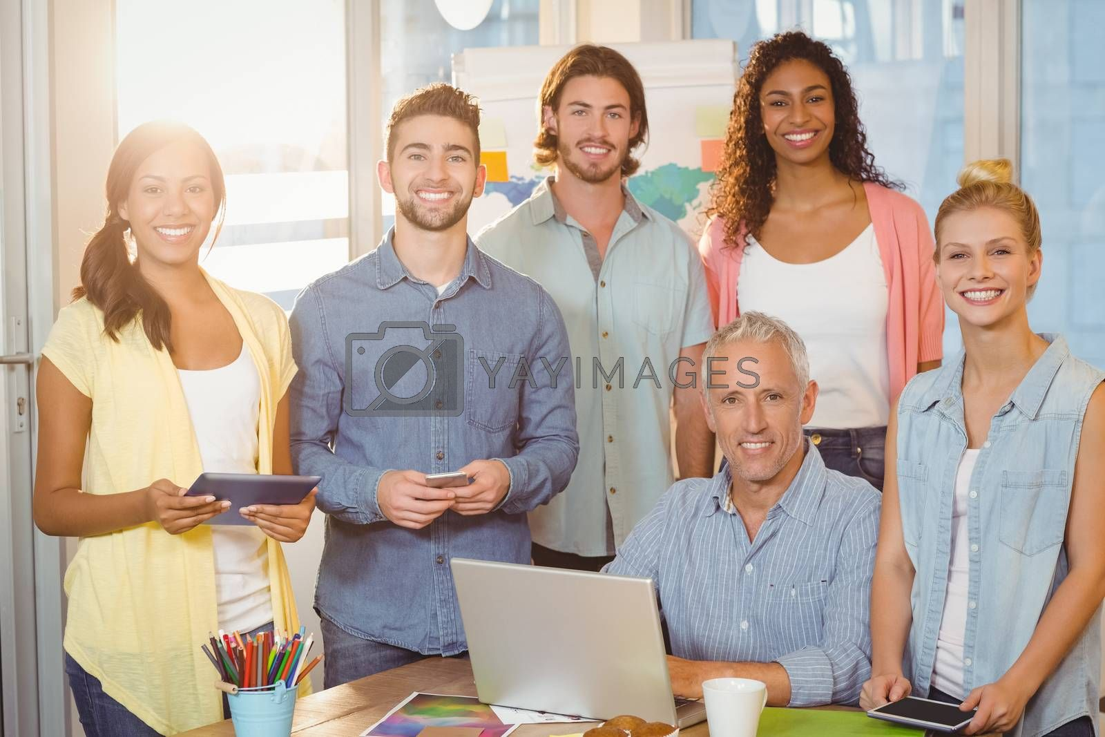 Portrait of smiling business people with technologies in meeting room at creative office
